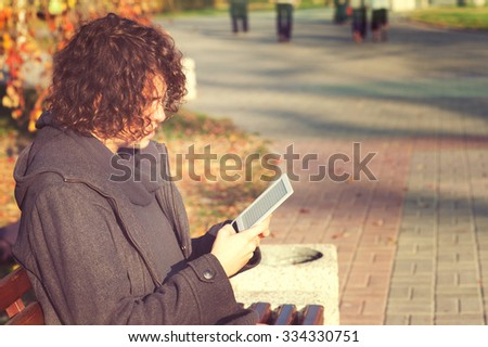 Young stylish man have a leisure sitting in autumn park and reading the electronic book. - stock photo