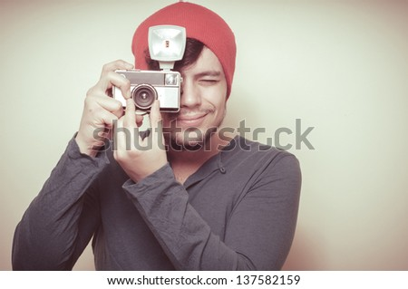 young stylish man holding old camera on vignetting background - stock photo