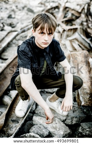 Young stylish man in khaki clothes posing in urban area