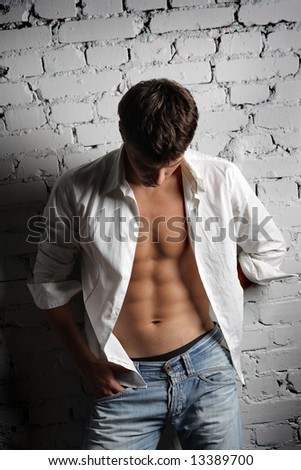 young stylish man in white shirt on a white break wall