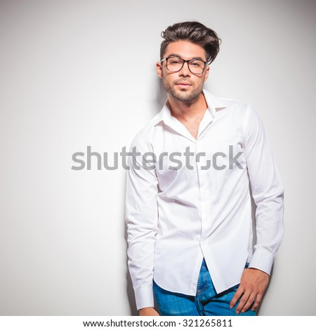 young stylish man looking at the camera while wearing glasses, white shirt and blue jeans