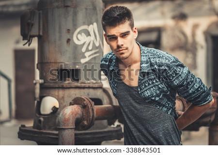 Young stylish man model posing near the metal loft tube. Fashion shot. man model sunglasses, man model casual, man model vogue, man handsome, man model sexy, man model shirt, man pose, man style - stock photo