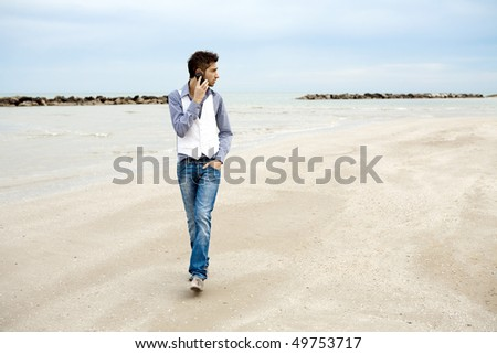 Young stylish man on the phone and walking on beach - stock photo