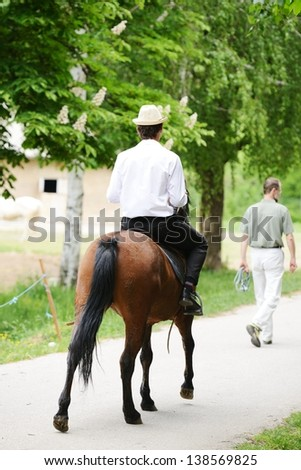Young stylish man taking riding a horse on countryside - stock photo