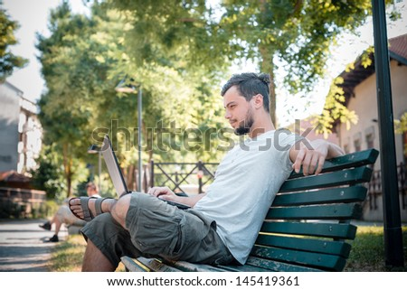 young stylish man using notebook at the park