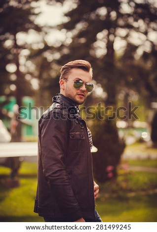 young stylish man with a beard walks in sunglasses outdoors - stock photo
