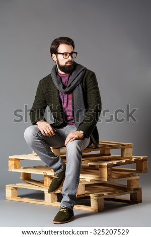 Young stylish man with a beard, wearing a jacket sitting on pallets - stock photo