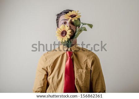 young stylish man with flowers on white background