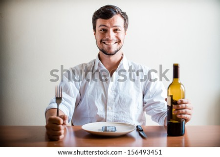 young stylish man with white shirt and phone on the dish behind a table