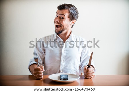 young stylish man with white shirt and phone on the dish behind a table - stock photo