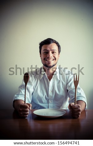 young stylish man with white shirt eating in mealtimes behind a table