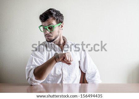 young stylish man with white shirt time wristwatch behind a table - stock photo