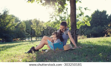 Young stylish mother and toddler reading book at garden during summer fun - stock photo