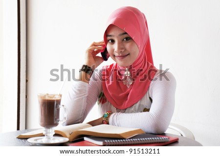 Young stylish muslim women talking on mobile phone at the cafe with books and drinks on the table