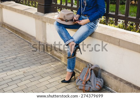 young stylish pretty woman, hands holding a phone, denim shirt and jeans, high heel shoes, hat, backpack, sunny day, good weather, city street, vacation europe, travel, detail, cool accessories - stock photo