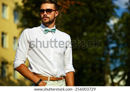 Young stylish sexy handsome model man in casual hipster cloth lifestyle in the street in sunglasses - stock photo