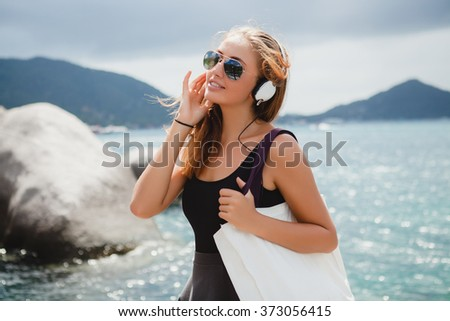 young stylish sexy hipster woman with a shopping bag during vacation, aviator sunglasses, headphones, listening to music, happy, enjoying sun, tropical island blue lagoon landscape - stock photo