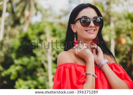 young stylish sexy woman in red summer dress standing on terrace in tropical hotel, palm trees background, long black hair, sunglasses, ethnic earrings, sunglasses, looking forward, smiling, close up - stock photo