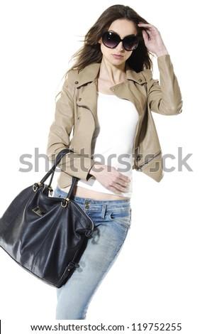 Young stylish slim in sunglasses with handbag posing - stock photo