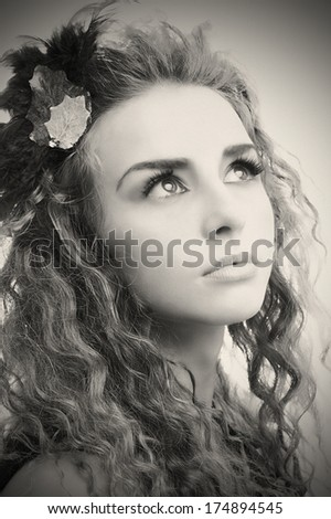 Young stylish teen portrait with artistic make-up and autumn leafs in her hair.Old black and white version. - stock photo