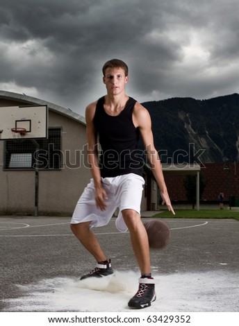 Young stylish teenage basketball player on the street with dark clouds over him. - stock photo