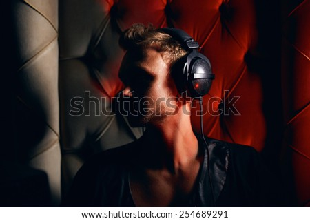 Young stylish trendy guy sitting musician DJ headphones for musical instruments and laptop with speakers - stock photo
