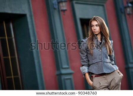 young stylish woman against old building wall - stock photo