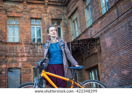 Young stylish woman and bike in city with old brick building on background - stock photo