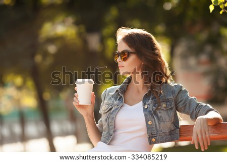 Young stylish woman drinking coffee to go in a park - stock photo