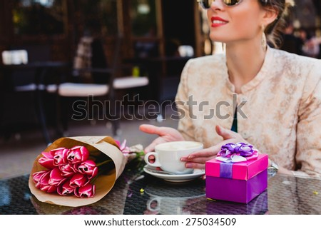 young stylish woman, fashion sunglasses sitting in cafe, holding drinking cup cappuccino, smiling, enjoying warm, presents, tulips, happy birthday party, city street, europe vacation, detail, close up - stock photo