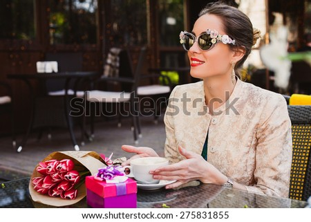 young stylish woman, fashion sunglasses sitting in cafe, holding drinking cup cappuccino, smiling, enjoying warm, presents, tulips, happy birthday party, city street, europe vacation, glamour outfit - stock photo