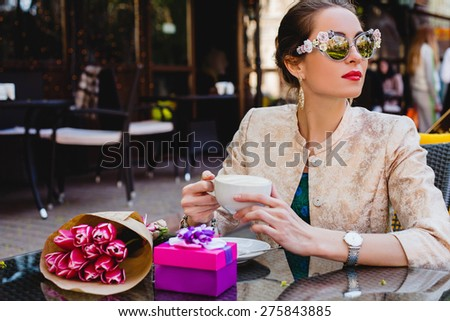 young stylish woman, fashion sunglasses sitting in cafe, holding drinking cup cappuccino, smiling, enjoying warm, presents, tulips, happy birthday party, city street, europe vacation - stock photo