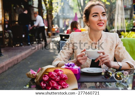 young stylish woman, fashion sunglasses, sitting in cafe, holding drinking cup cappuccino, tulips, happy birthday party, city street, boho outfit, europe vacation, romantic dinner, sunny, smiling - stock photo