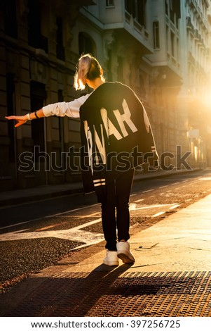 Young stylish woman hitchhiking along the road on the street at sunset. - stock photo