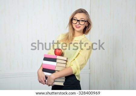 Young stylish woman holding a lot of books and an apple. The concept for the advertising information about education and training. Business woman with glasses. Clever girl. University student. - stock photo