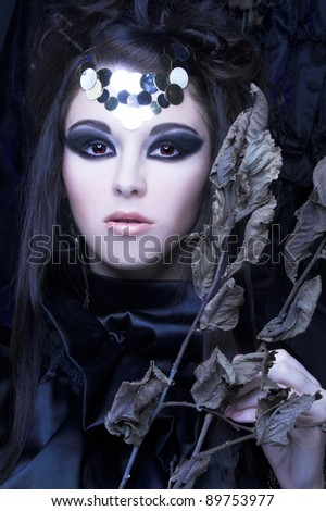Young stylish woman in black dress with artistic visage with  branch with dry leafs