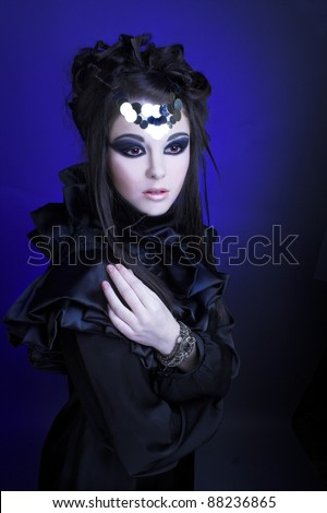 Young stylish woman in black dress with artistic visage with smokey-eyes - stock photo