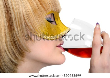 young stylish woman in carnival mask drinks red wine, isolated on white