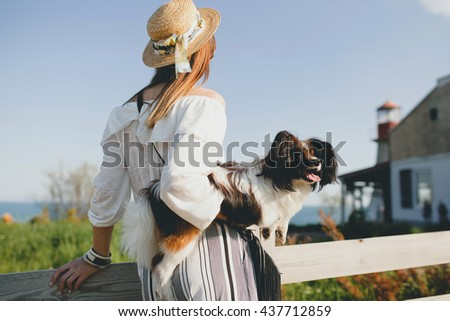 young stylish woman in countryside, looking forward, holding a dog, happy positive mood, summer, straw hat, bohemian style outfit, view from back - stock photo