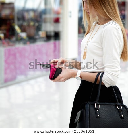 Young stylish woman in cute trendy outfit with leather handbag looking into purse. Close-up on hands with wallet - stock photo