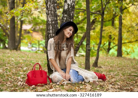 Young stylish woman in hat resting in the autumn park on the background of a birchwood - stock photo