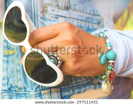 Young stylish woman in jeans vest  with white heart shaped sunglasses, retro bracelet with turquoise stone, retro ring with turquoise blue stone,summer  fashion concept in sunny day - stock photo