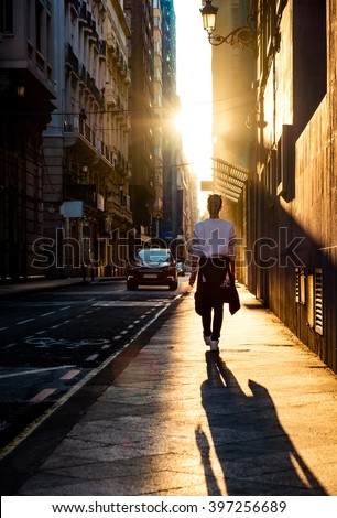 Young stylish woman walking by the road on the street at sunset.