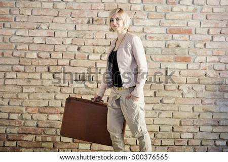Young stylish woman walking, holding suitcase front of brick wall.