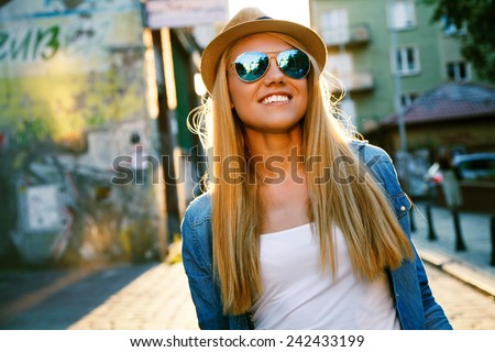 Young stylish woman walking in a city street - stock photo