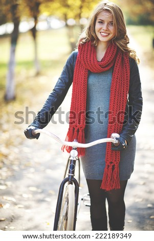 Young stylish woman walking with bike in autumn - stock photo