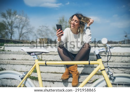 Young stylish woman with a bicycle using cell phone - stock photo