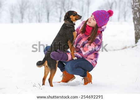 Young stylish woman with a dog having fun in a winter forest. - stock photo