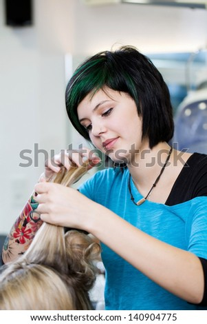 young stylist with tattoo at work in salon - stock photo