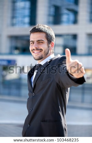 young success businessman showing thumbs-up sign, outdoor